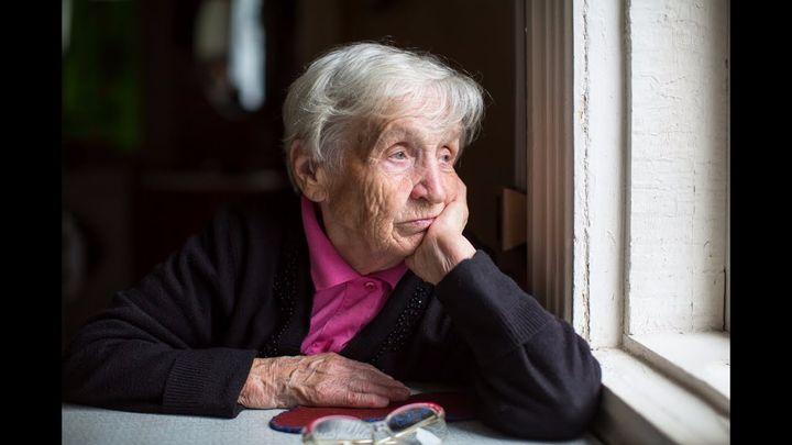Femme âgée par la fenêtre